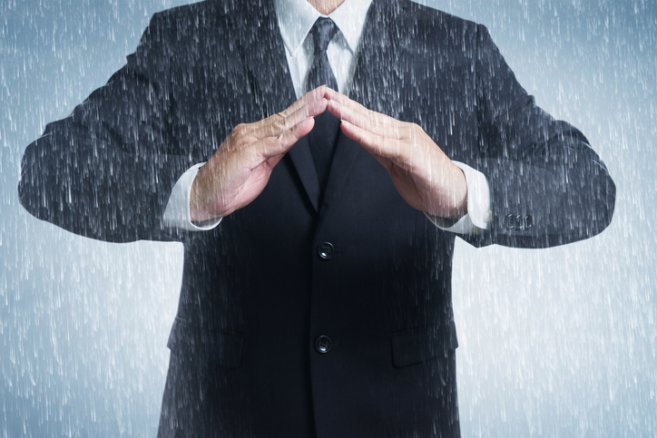 Businessman in suit with two hands in position to protect in rainy weather day (focus on hand, blur out the suit). It indicates many aspects such as car insurance coverage, support, assurance, reliability.